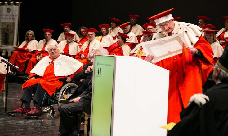 Bertolucci (left, in wheelchair) receiving an honorary degree from the University of Parma