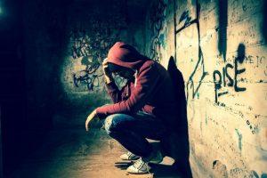 Homeless-boy-on-graffiti-wall