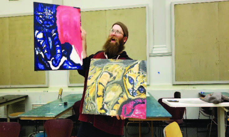 Ryan-McCormick-with-2-of-his-paintings