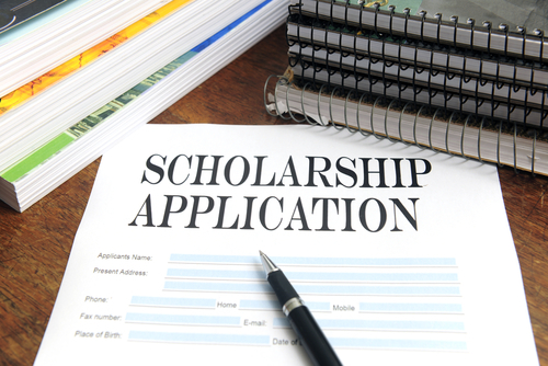scholarship application and pen on desk surrounded by notebooks