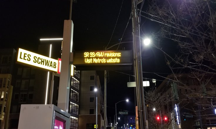 bus stop announcement sign stating to visit the king county website for sr99 route revisions