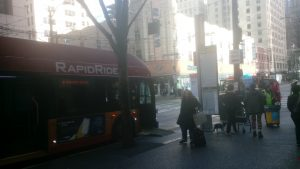 Rider boarding bus on Third Ave in downtown Seattle